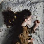 Ein Kind liegt auf dem Bett und schläft.